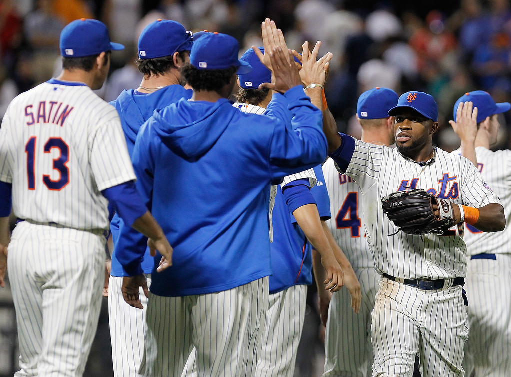 . Eric Young Jr. #22 of the New York Mets celebrates with teammates after defeating the Colorado Rockies at Citi Field on August 6, 2013 at Citi Field in the Flushing neighborhood of the Queens borough of New York City. Mets defeated the Rockies 3-2.  (Photo by Mike Stobe/Getty Images)
