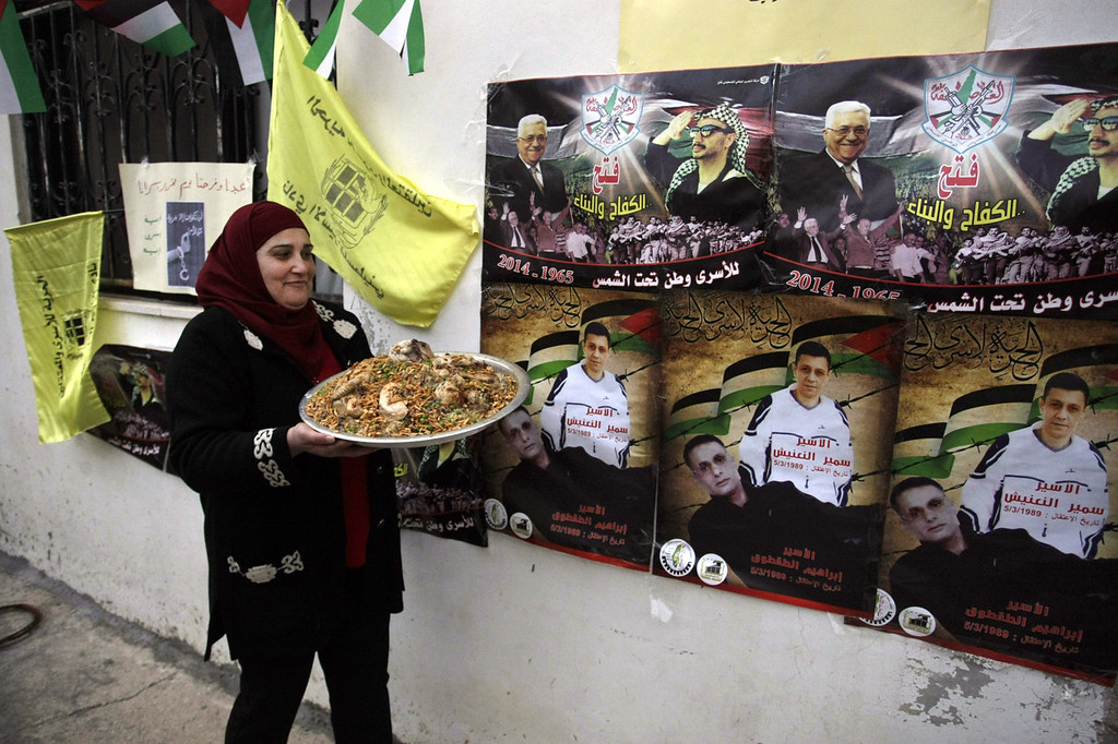 """. A Palestinian relative of Ibrahim Taqtoq, carries a dish with chicken and rice as she walks past posters of Palestinian President Mahmoud Abbas and late Palestinian leader Yasser Arafat with Arabic that reads, \""""Fatah, struggling and building,\"""" top, and \""""prisoner Samir Al-Naanish, prisoner Ibrahim Taqtoq,\"""" bottom, in the West Bank city of Nablus, Monday, Dec. 30, 2013. Israel and the Palestinians are gearing up for the expected release by Israel of 26 of the longest-serving Palestinian prisoners. Israel has agreed to release the men, who were all convicted in deadly attacks of Israelis, as part of a U.S.-brokered package to restart peace talks. (AP Photo /Nasser Ishtayeh)"""