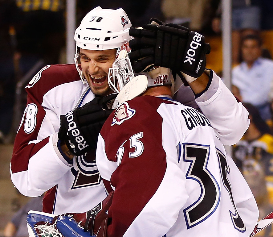 . Patrick Bordeleau #58 of the Colorado Avalanche celebrates with teammate Jean-Sebastien Giguere #35 following a 2-0 win against the Boston Bruins at the end of the third period during the game on October 10, 2013 at TD Garden in Boston, Massachusetts. (Photo by Jared Wickerham/Getty Images)