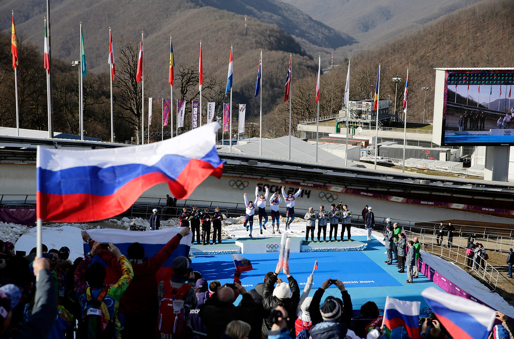 . The team from Russia RUS-1, with Alexander Zubkov, Alexey Negodaylo, Dmitry Trunenkov, and Alexey Voevoda, jump onto the medal stand after they won the gold medal during the men\'s four-man bobsled competition final at the 2014 Winter Olympics, Sunday, Feb. 23, 2014, in Krasnaya Polyana, Russia. (AP Photo/Jae C. Hong)