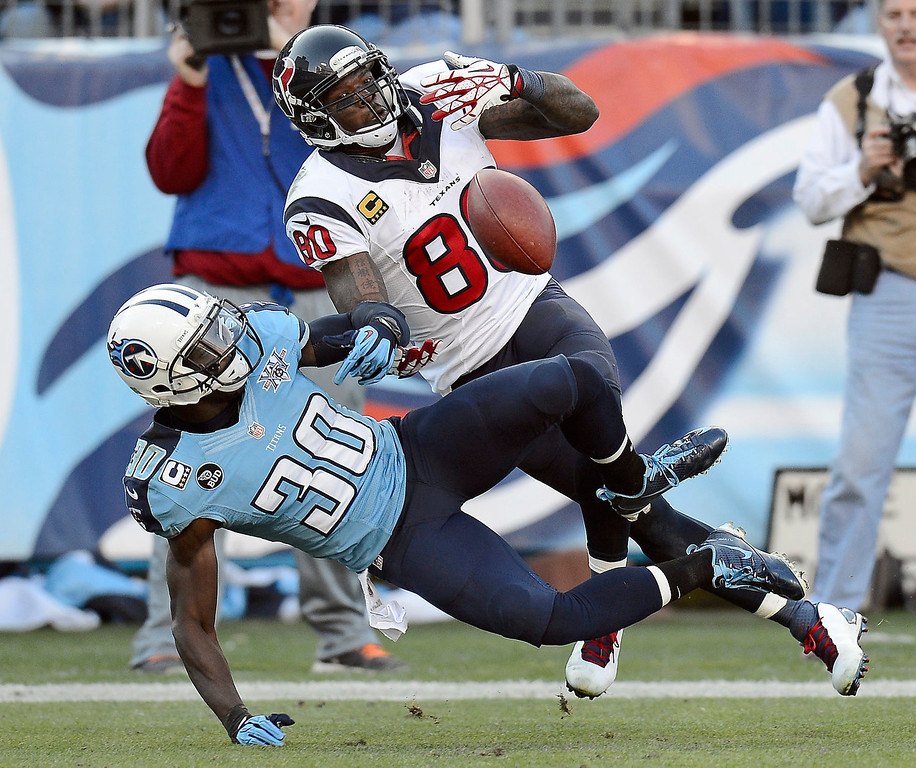 . Tennessee Titans cornerback Jason McCourty (30) breaks up a pass intended for Houston Texans wide receiver Andre Johnson (80) in the fourth quarter of an NFL football game Sunday, Dec. 29, 2013, in Nashville, Tenn. (AP Photo/Mark Zaleski)