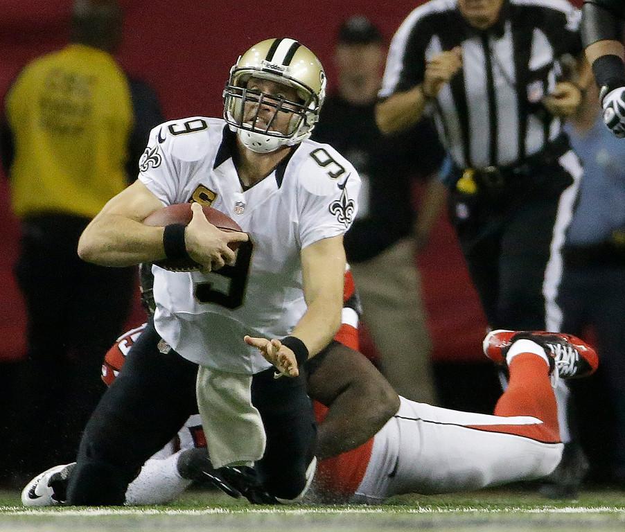 . Atlanta Falcons running back Antone Smith (35) tackles New Orleans Saints quarterback Drew Brees (9) during the first half of an NFL football game, Thursday, Nov. 21, 2013, in Atlanta. (AP Photo/David Goldman)