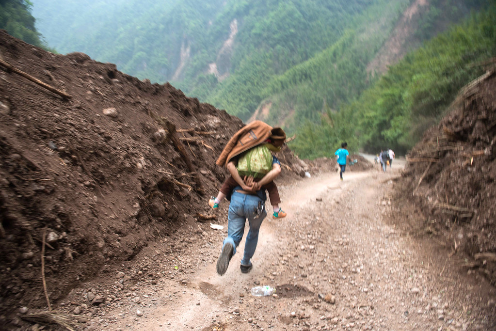 . This photo taken on April 21, 2013 shows a man running with his daughter on his back during aftershocks to avoid falling rocks on their way to the city of Ya\'an, southwest China\'s Sichuan province.           STR/AFP/Getty Images