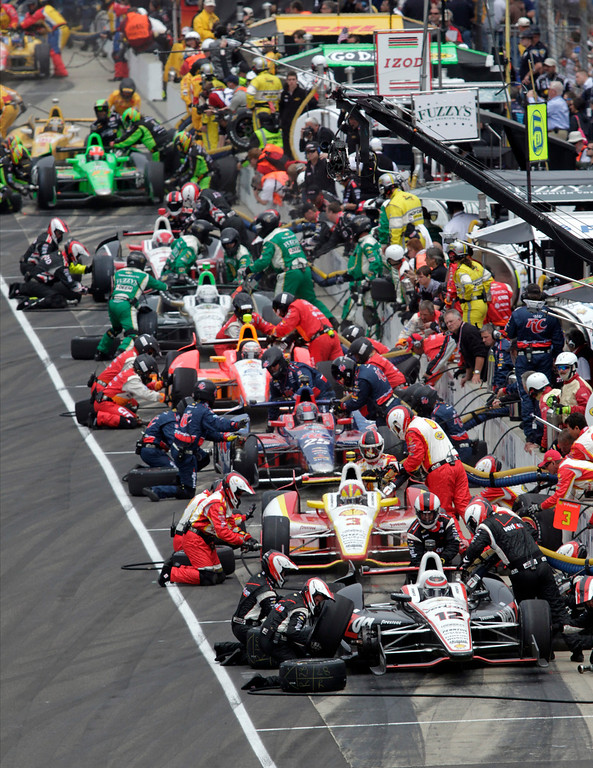 . Teams, including those of Australia\'s Will Power (12) and Brazil\'s Helio Castroneves (3), pit during a yellow flag on lap 58 of the Indianapolis 500 auto race at the Indianapolis Motor Speedway in Indianapolis, Sunday, May 26, 2013. (AP Photo/AJ Mast)