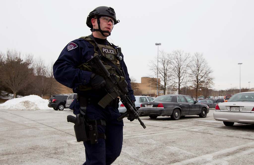 . Police move in from a parking lot to the Mall in Columbia after reports of a multiple shooting, Saturday Jan. 25, 2014 Howard County, Md.  Police in Maryland say three people died Saturday in a shooting at a mall in suburban Baltimore, including the presumed gunman.  ( AP Photo/Jose Luis Magana)