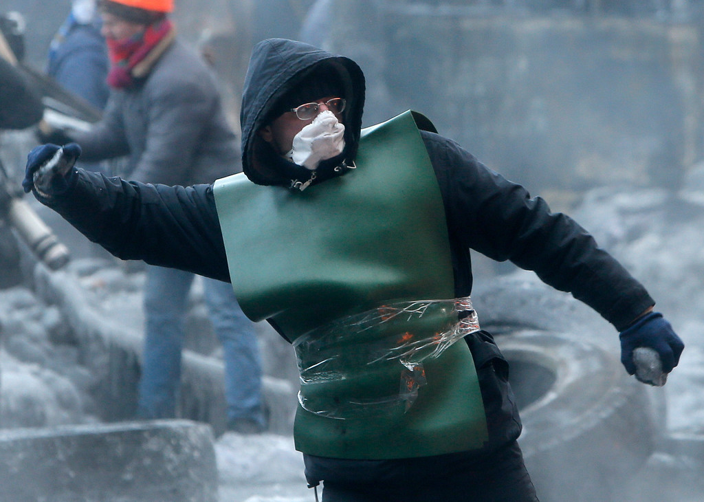 . A protester throws a stone towards riot police during a clash in central Kiev, Ukraine, Saturday Jan. 25, 2014. Ukraine\'s Interior Ministry has accused protesters in Kiev of capturing two of its officers as violent clashes have resumed in the capital and anti-government riots spread across Ukraine. (AP Photo/Efrem Lukatsky)