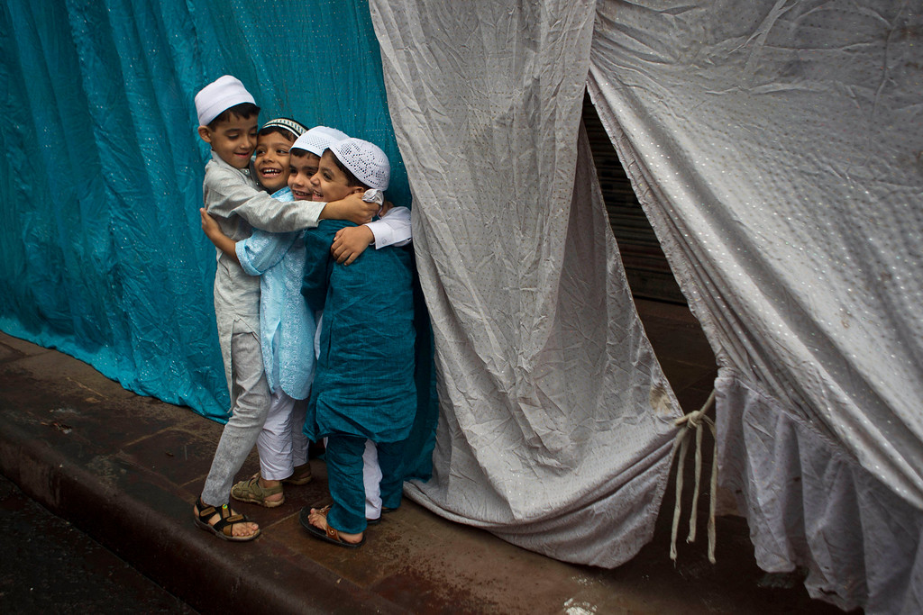 . Indian Muslim children hug and wish each other after offering Eid prayers in New Delhi, India, Friday, Aug. 9, 2013. Eid al-Fitr marks the end of the holy month of Ramadan, during which Muslims all over the world fast from sunrise to sunset. (AP Photo/Tsering Topgyal)
