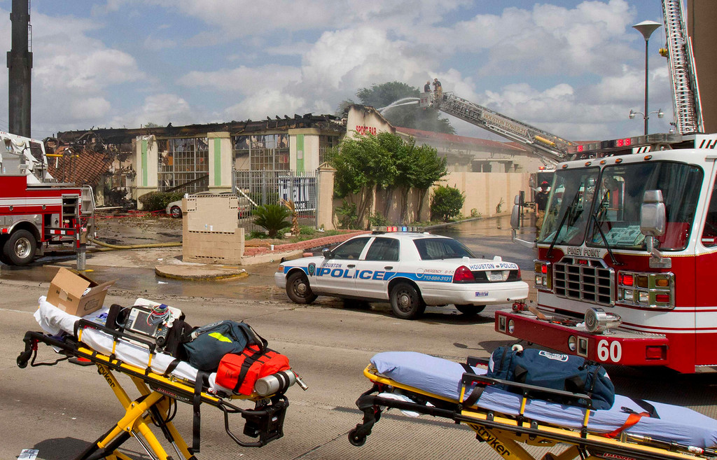 . Firefighters work the scene of a five-alarm fire where four firefighters were killed battling the blaze at a restaurant and hotel in southwest Houston May 31, 2013.     REUTERS/Richard Carson