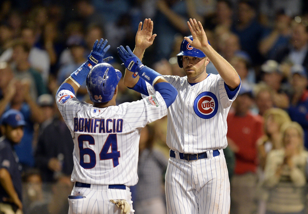 . Nate Schierholtz #19 of the Chicago Cubs high-fives teammate Emilio Bonifacio #64 after Bonifacio hit a two-run home run scoring Schierholtz during the fourth inning against the Colorado Rockies on July 29, 2014 at Wrigley Field in Chicago, Illinois.  (Photo by Brian Kersey/Getty Images)