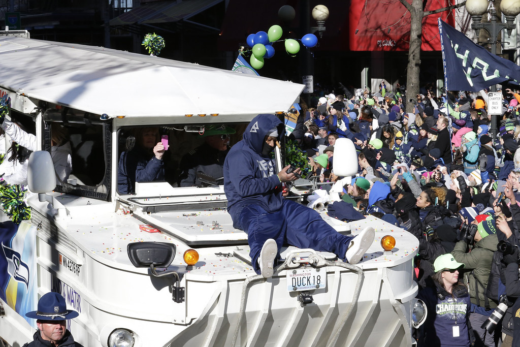 . Seattle Seahawks running back Marshawn Lynch rides on the hood of a vehicle during the parade for the NFL football Super Bowl champions, Wednesday, Feb. 5, 2014, in Seattle.  (AP Photo/Ted S. Warren)