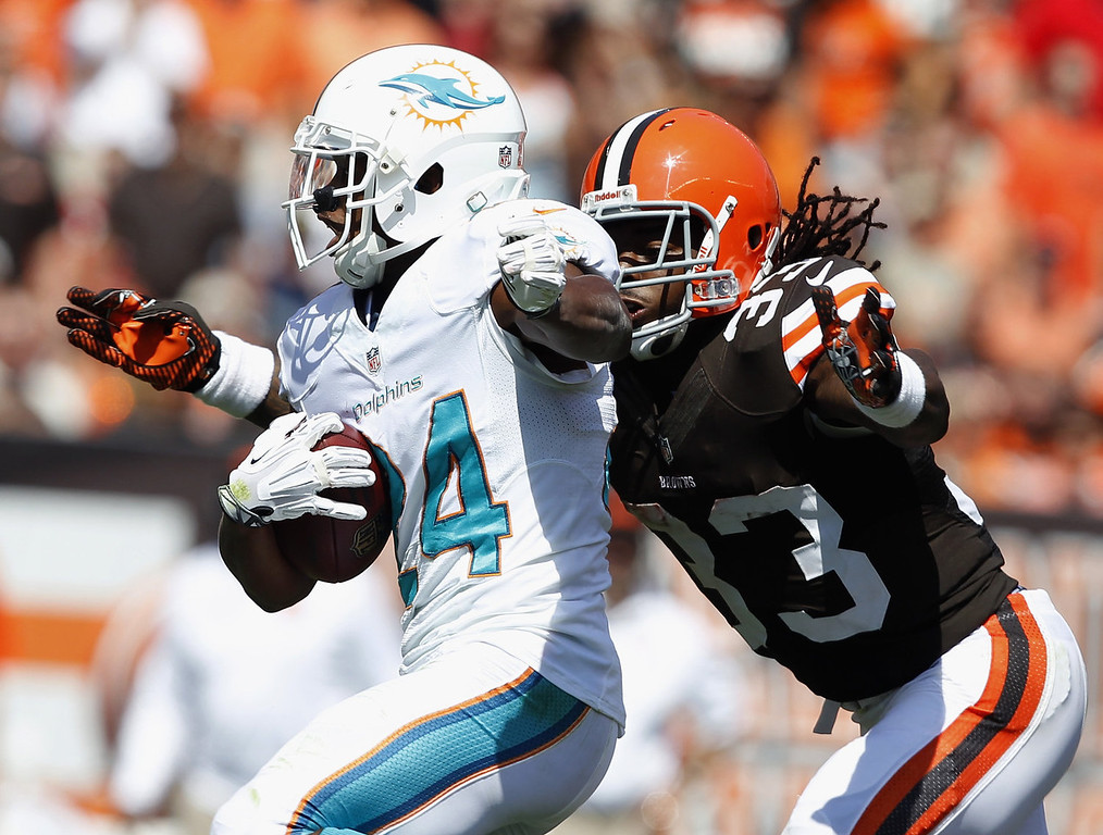 . Cornerback Dimitri Patterson #24 of the Miami Dolphins runs by running back Trent Richardson #33 of the Cleveland Browns at Cleveland Browns Stadium on September 8, 2013 in Cleveland, Ohio. (Photo by Matt Sullivan/Getty Images)