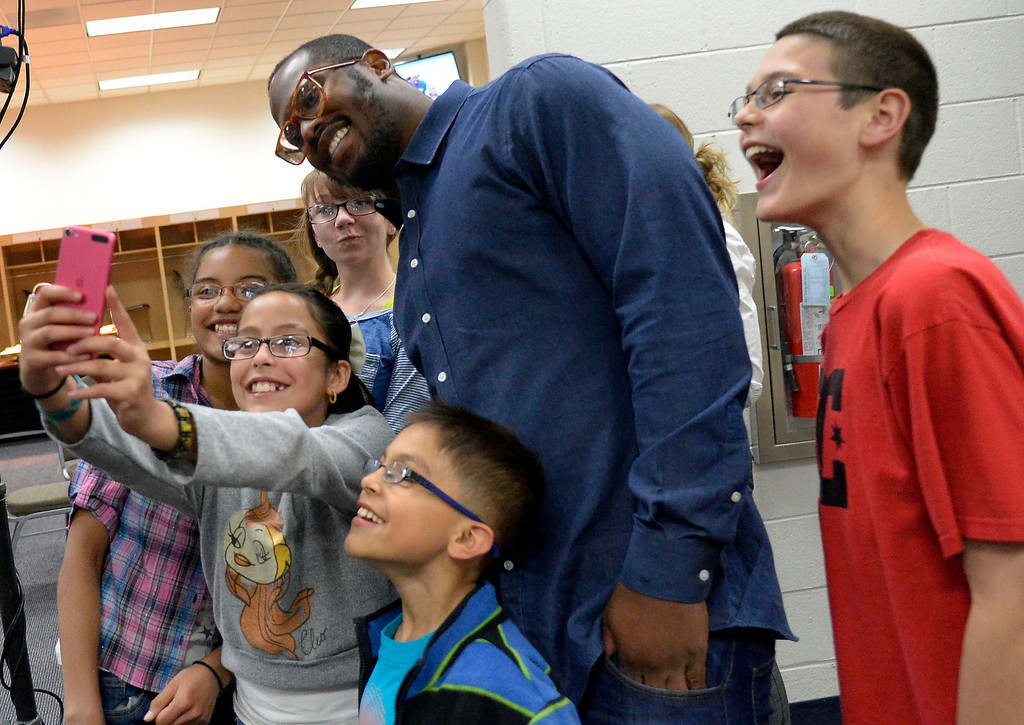 . Sofia Martinez, 10, takes a group selfie with Denver Broncos linebacker Von Miller after they received their prescription glasses April 14, 2014. Miller\'s Foundation, Von\'sVision, distributed prescription glass to more than 100 underprivileged children at Sports Authority Field. (Photo by John Leyba/The Denver Post)
