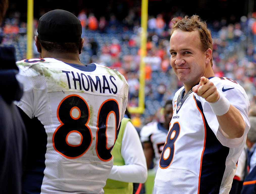 . Denver Broncos quarterback Peyton Manning (18) points over with a smile after talking to Broncos tight end Julius Thomas (80) on the bench after throwing his record breaking 51st pass to him for a touchdown in the fourth quarter against the Houston Texans December 22, 2013 at Reliant Stadium. (Photo by John Leyba/The Denver Post)