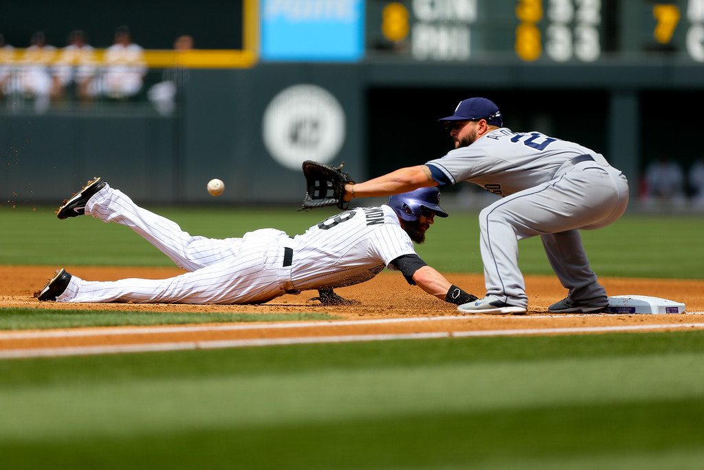 . Charlie Blackmon #19 of the Colorado Rockies dives safely back into first base as first baseman Yonder Alonso #23 of the San Diego Padres receives the throw during the first inning at Coors Field on May 18, 2014 in Denver, Colorado. (Photo by Justin Edmonds/Getty Images)