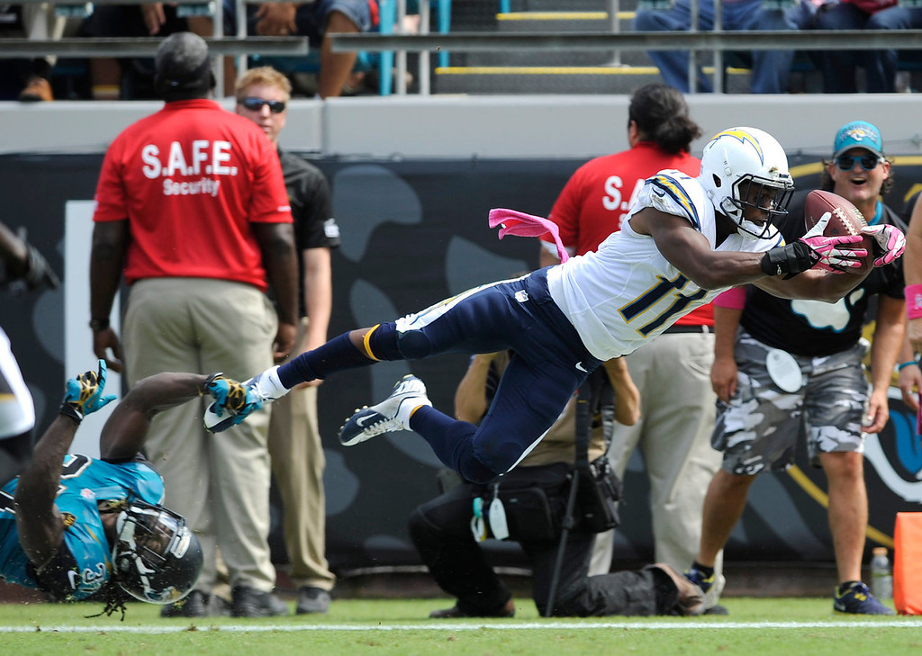 . San Diego Chargers wide receiver Eddie Royal (11) catches a 27-yard pass for a touchdown as Jacksonville Jaguars strong safety Johnathan Cyprien, lower left, can\'t stop him during the first half of an NFL football game in Jacksonville, Fla., Sunday, Oct. 20, 2013.(AP Photo/Stephen Morton)