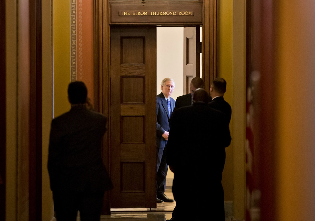 . Senate Minority Leader Mitch McConnell, R-Ky., shown center, summons GOP senators to a closed-door meeting at the Capitol in Washington, Wednesday, Oct. 16, 2013. Sen. McConnell and his Democratic counterpart, Senate Majority Leader Harry Reid, D-Nev., are optimistic about forging an eleventh-hour bipartisan deal preventing a possible federal default and ending the partial government shutdown after Republican divisions forced GOP leaders to drop efforts to ram their own version through the House.  (AP Photo/J. Scott Applewhite)