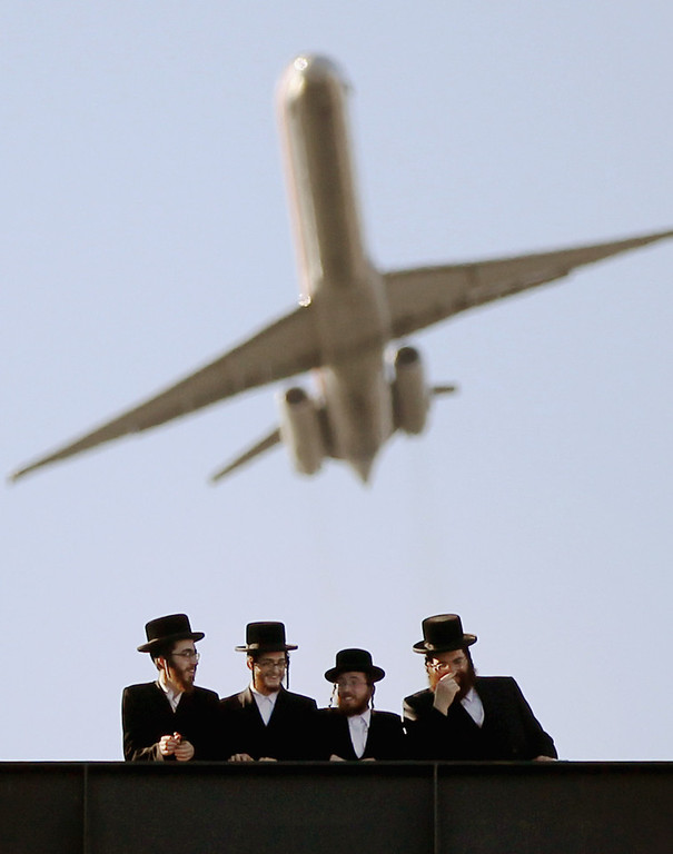 . Ultra-Orthodox Jews gather at Citi Field as a plane takes off overhead from LaGuradia Airport at a meeting to discuss the risks of using the Internet on May 20, 2012 in the Queens borough of New York City. More than 40,000 were expected to attend the rally at Citi Field, the home of the New York Mets, which organizers said would promote religiously responsible ways to use the Internet.  (Photo by Mario Tama/Getty Images)