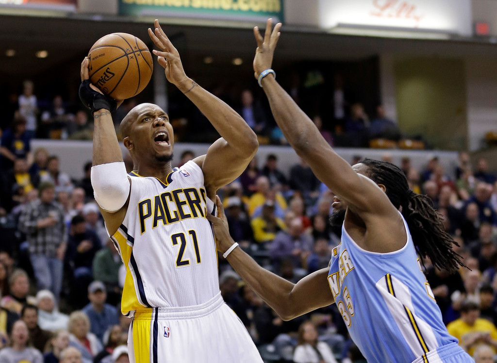 . Indiana Pacers forward David West (21) shoots over Denver Nuggets forward Kenneth Faried in the second half of an NBA basketball game in Indianapolis, Monday, Feb. 10, 2014. The Pacers defeated the Nuggets 119-80.  (AP Photo/Michael Conroy)