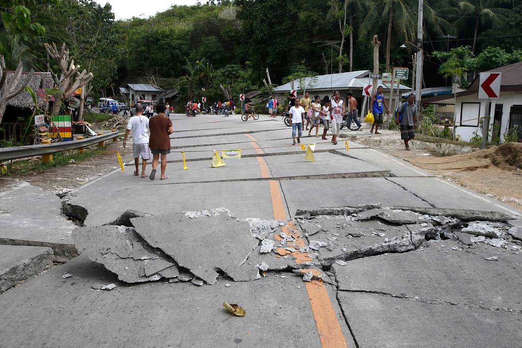 . Residents go about their daily business while walking on a road damaged in Tuesday\'s 7.2-magnitude earthquake in Maribojoc township, Bohol province in central Philippines Wednesday, Oct. 16, 2013.   (AP Photo/Bullit Marquez)