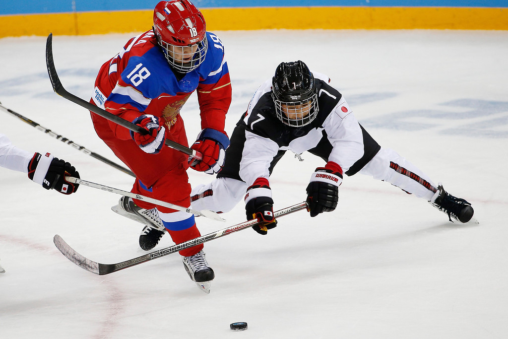 . Olga Sosina of Russia and Mika Hori of Japan battle for control of the puck during the 2014 Winter Olympics women\'s ice hockey game at Shayba Arena Sunday, Feb. 16, 2014, in Sochi, Russia. (AP Photo/Petr David Josek)