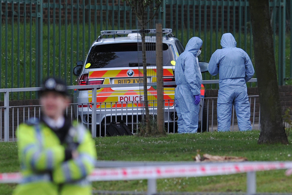 . Police forensics officers search a cordoned off area in Woolwich, east London, on May 22, 2013, following an incident in which one man was killed and two others seriously injured.    AFP PHOTO / CARL COURT/AFP/Getty Images
