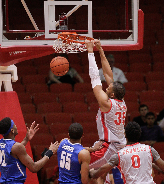 . Houston\'s forward TaShawn Thomas  (35) dunks on Memphis\' Geron Johnson (55) during the first half of an NCAA college basketball game, Thursday, Feb. 27, 2014, in Houston. (AP Photo/Bob Levey)