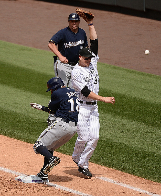 . DENVER, CO - JUNE 210: Colorado infielder Josh Rutledge, not pictured, threw high to first base allowing Milwaukee\'s Khris Davis to advance to second base in the second inning. The Colorado Rockies hosted the Milwaukee Brewers at Coors Field Saturday afternoon, June 21, 2014. Photo by Karl Gehring/The Denver Post