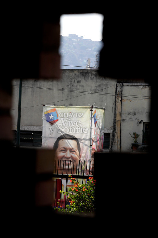 ". A poster of Venezuela\'s President Hugo Chavez is seen through a cross-shaped window, from inside the military hospital\'s chapel, in Caracas, Venezuela, Tuesday, March 5, 2013. A brief statement read on national television by Communications Minister Ernesto Villegas late Monday carried the sobering news about the charismatic 58-year-old leader\'s deteriorating health. Villegas said Chavez is suffering from ""a new, severe infection.\"" The state news agency identified it as respiratory. (AP Photo/Ariana Cubillos)"