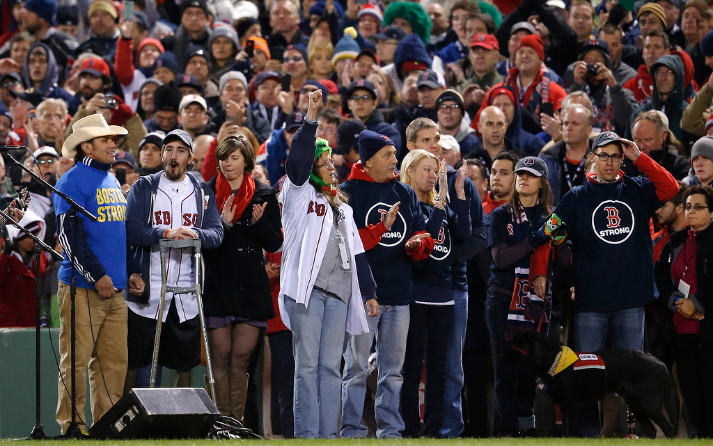 . Carlos Arredondo, left, and Boston Marathon bombing survivor Jeff Bauman, second from left, stand with other Boston Marathon bombing survivors during the seventh inning stretch of Game 2 of baseball\'s World Series between the Boston Red Sox and the St. Louis Cardinals Thursday, Oct. 24, 2013, in Boston. (AP Photo/Elise Amendola)