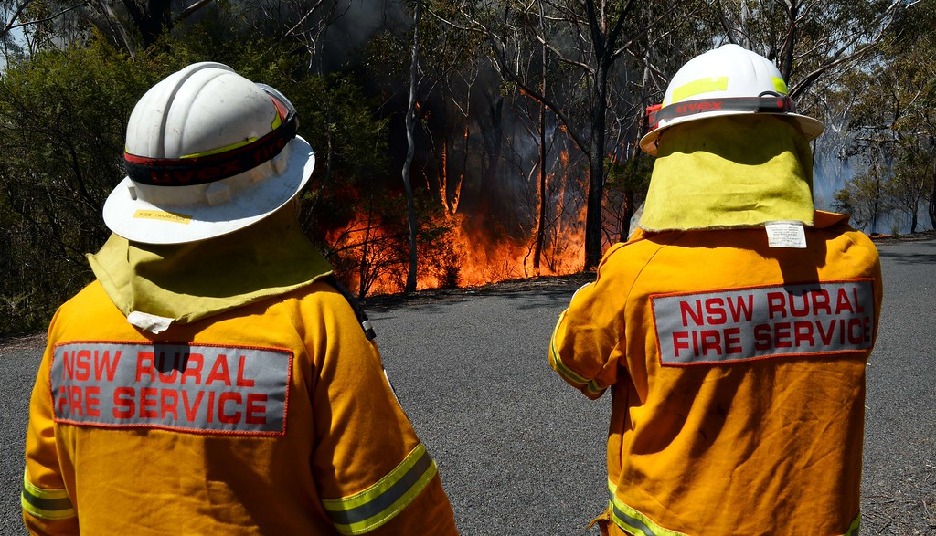 ". Firefighters monitor a back burn near Mount Victoria in the Blue Mountains on October 21, 2013, as volunteer fire brigades race to tame an enormous blaze, with officials warning it could merge with others to create a ""mega-fire\"" if weather conditions worsen.    AFP PHOTO/William WEST/AFP/Getty Images"