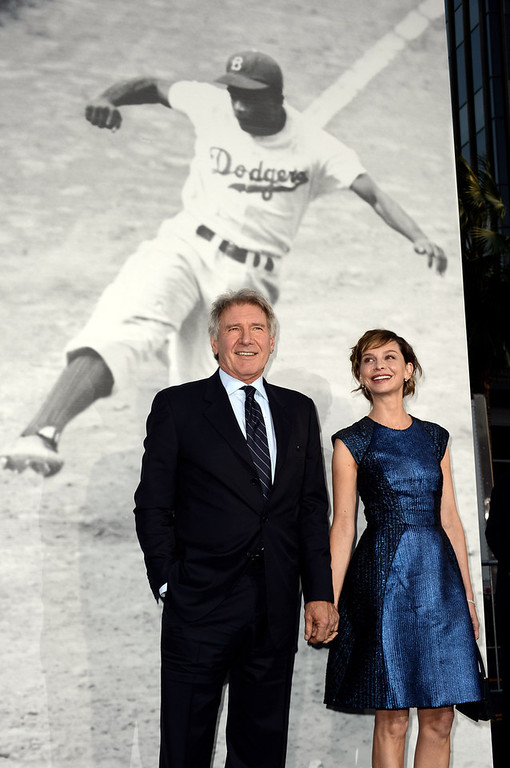 ". Actor Harrison Ford (L) and his wife actress Calista Flockhart arrive at the premiere of Warner Bros. Pictures\' and Legendary Pictures\' ""42\"" at the Chinese Theatre on April 9, 2013 in Los Angeles, California.  (Photo by Kevin Winter/Getty Images)"