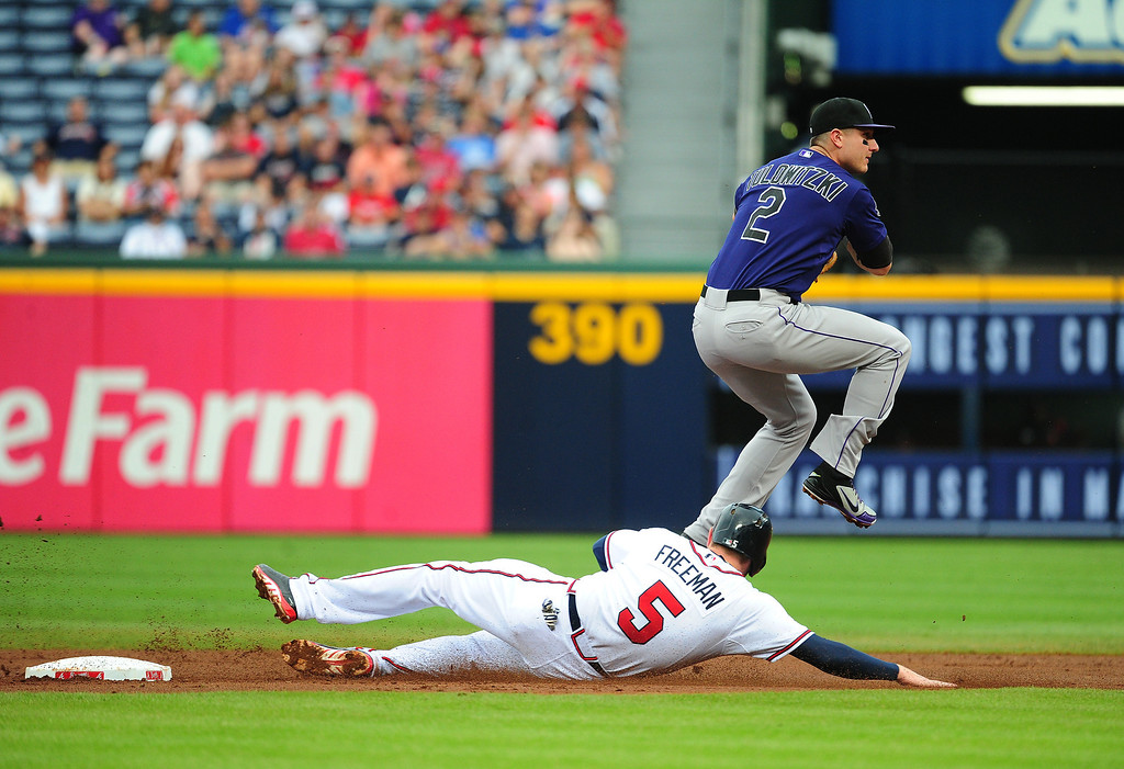 . Troy Tulowitzki #2 of the Colorado Rockies turns a double play against Freddie Freeman #5 of the Atlanta Braves at Turner Field on July 31, 2013 in Atlanta, Georgia. (Photo by Scott Cunningham/Getty Images)