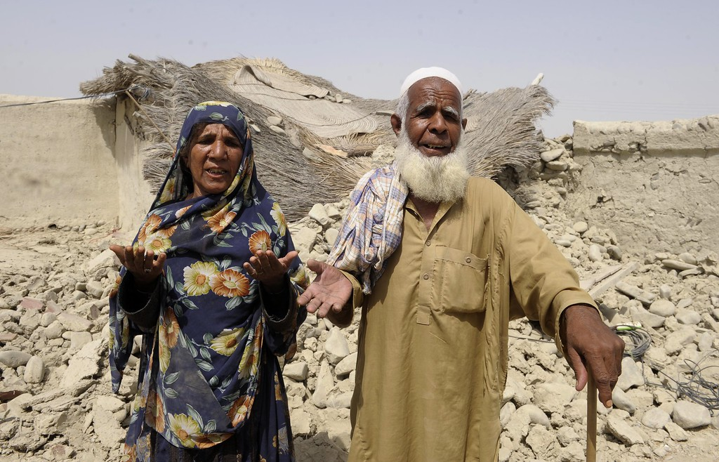 . Pakistani elderly earthquake survivors gesture in front of their destroyed  house in the devastated district of Awaran on September 25, 2013. A powerful 6.8-magnitude earthquake hit southwest Pakistan, in a region already devastated by a tremor which left more than 300 people dead and 100,000 homeless less than a week ago.  BANARAS KHAN/AFP/Getty Images