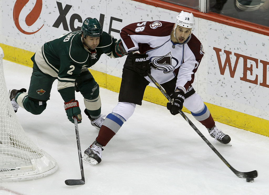 . Colorado Avalanche left wing Patrick Bordeleau (58) controls the puck past Minnesota Wild defenseman Keith Ballard (2) during the first period of an NHL hockey game in St. Paul, Minn., Friday, Nov. 29, 2013. (AP Photo/Ann Heisenfelt)
