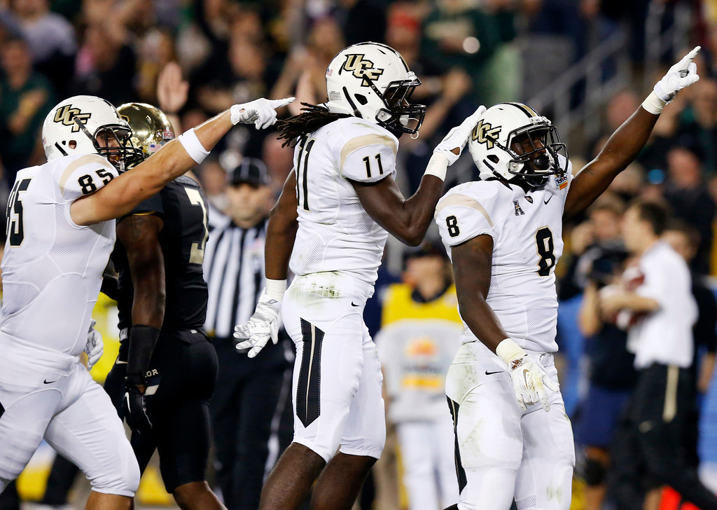. Central Florida running back Storm Johnson (8) celebrates after scoring a touchdown with teammates Breshad Perriman (11) and Kevin Miller (85) during the first half of the Fiesta Bowl NCAA college football game against Baylor, Wednesday, Jan. 1, 2014, in Glendale, Ariz. (AP Photo/Ross D. Franklin)