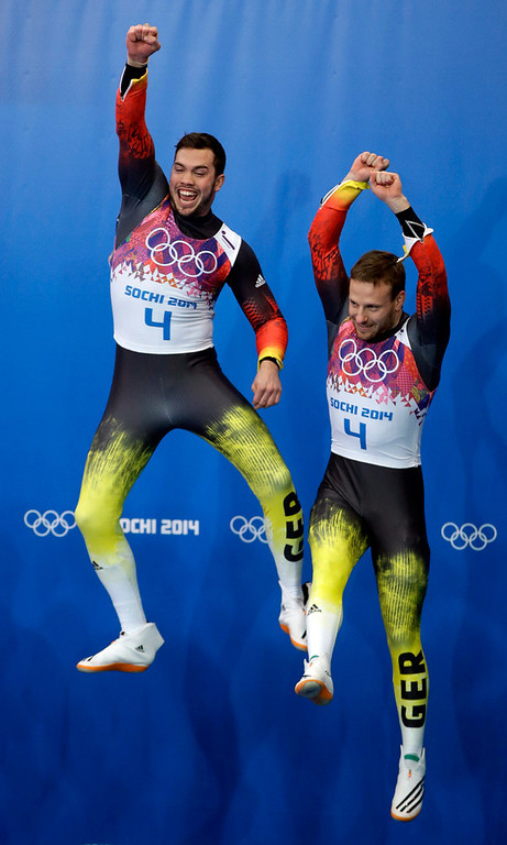 . The doubles team of Tobias Wendl and Tobias Arlt from Germany jump onto the podium for the flower ceremony after they won the gold medal during the men\'s doubles luge at the 2014 Winter Olympics, Wednesday, Feb. 12, 2014, in Krasnaya Polyana, Russia. (AP Photo/Dita Alangkara)