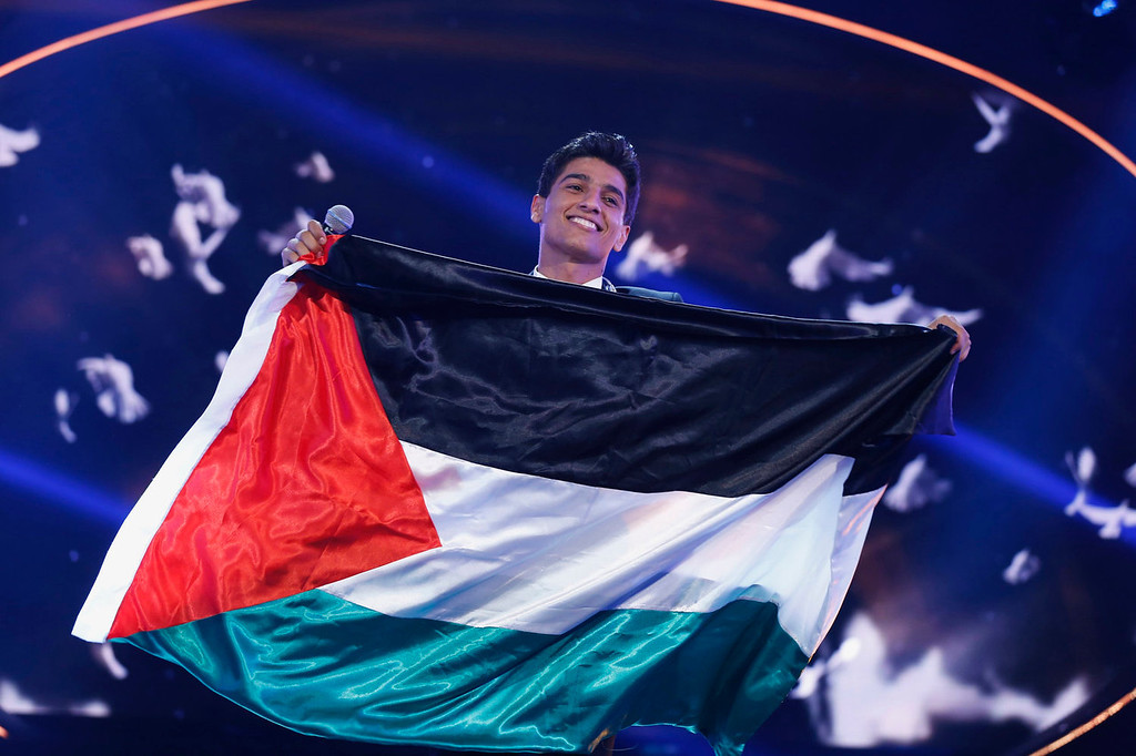 ". Palestinian singer Mohammed Assaf holds the Palestinian flag, as he stands on stage after being announced winner during the Season 2 finale of ""Arab Idol\"" in Zouk Mosbeh area, north of Beirut June 22, 2013.  REUTERS/Mohammed Azakir"
