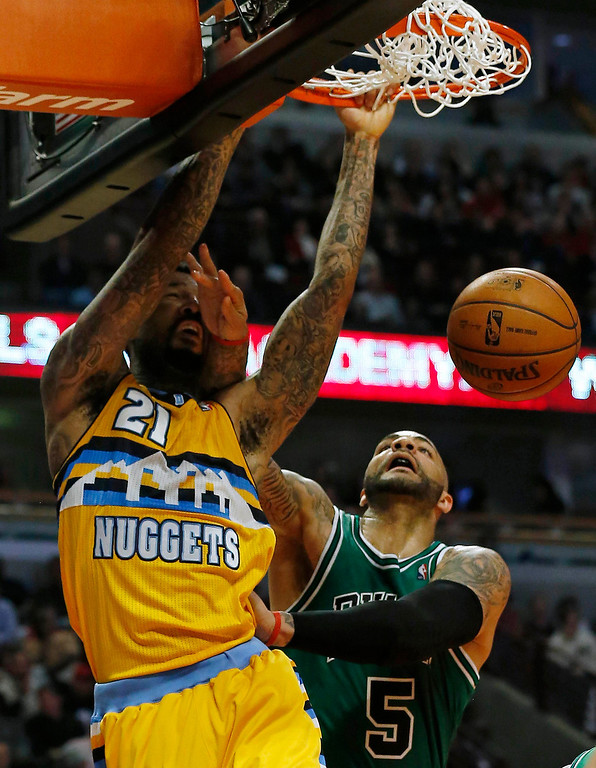 . Denver Nuggets\' Wilson Chandler goes to the basket against Chicago Bulls\' Carlos Boozer (R) during the first half of their NBA basketball game in Chicago, Illinois March 18, 2013. REUTERS/Jim Young