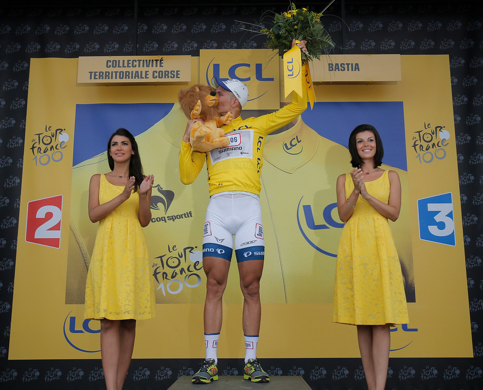 . Marcel Kittel of Germany, wearing the overall leader\'s yellow jersey, kisses the trophy on the podium of the first stage of the Tour de France cycling race over 213 kilometers (133 miles) with start in Porto Vecchio and finish in Bastia, Corsica island, France, Saturday June 29, 2013. (AP Photo/Christophe Ena)