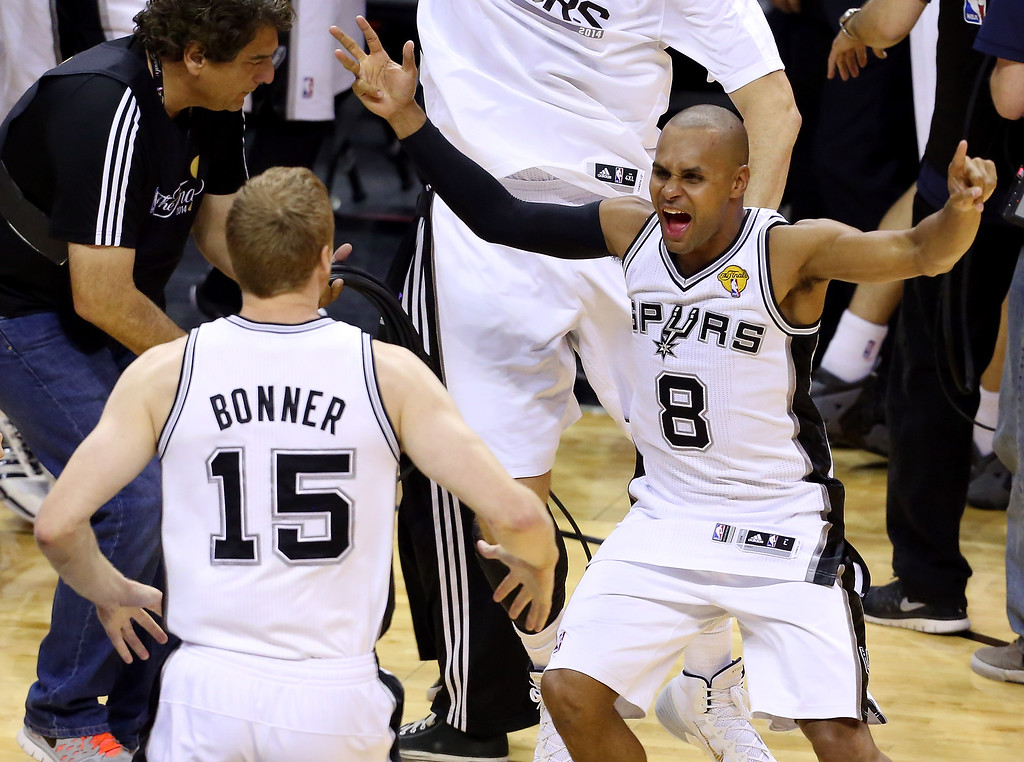 . Patty Mills #8 celebrates with Matt Bonner #15 of the San Antonio Spurs after defeating the Miami Heat in Game Five of the 2014 NBA Finals at the AT&T Center on June 15, 2014 in San Antonio, Texas.  (Photo by Chris Covatta/Getty Images)