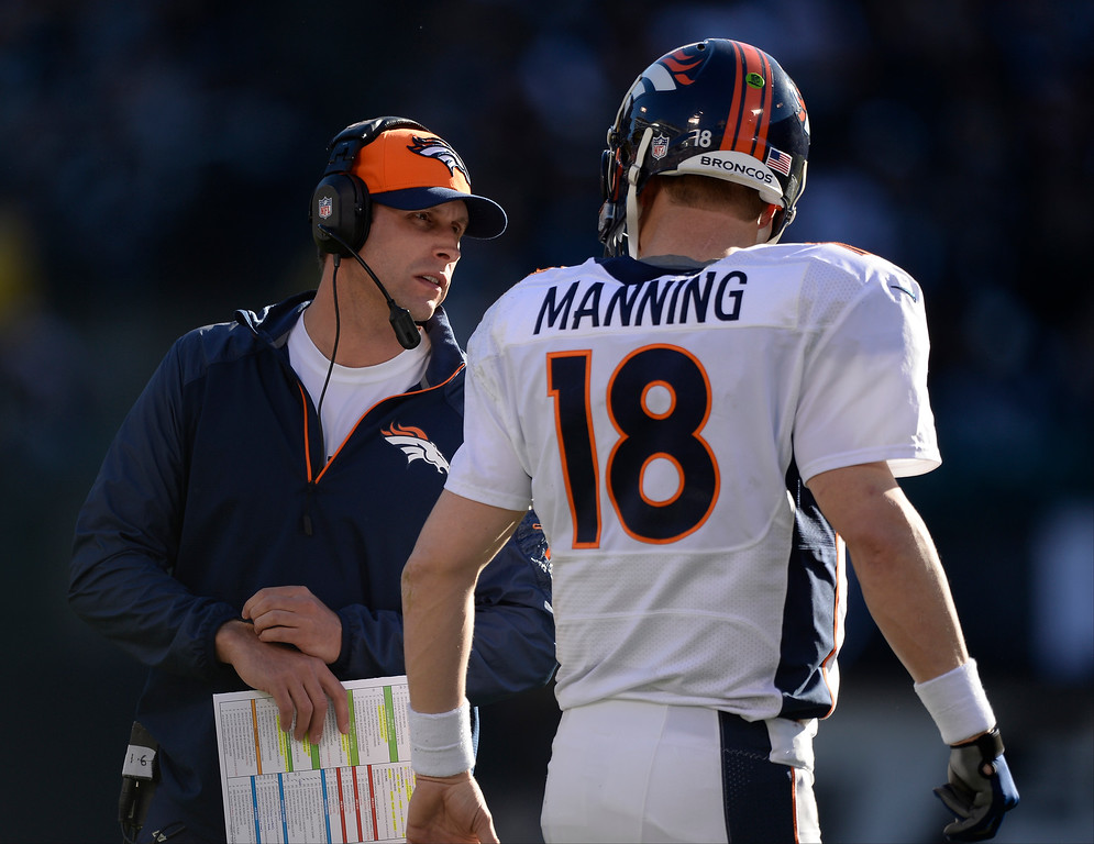 . Denver Broncos Adam Gase talks with Denver Broncos quarterback Peyton Manning (18) during a timeout against the Oakland Raiders in the second quarter at O.co Coliseum. (Photo by John Leyba/The Denver Post)