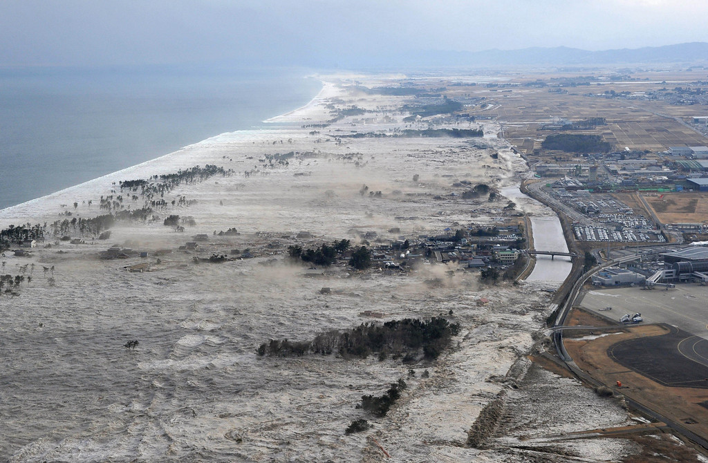 . Earthquake-triggered tsumanis sweep shores along Iwanuma in northern Japan on Friday March 11, 2011. The magnitude 8.9 earthquake slammed Japan\'s eastern coast Friday, unleashing a 13-foot (4-meter) tsunami that swept boats, cars, buildings and tons of debris miles inland.  (AP Photo/Kyodo News)