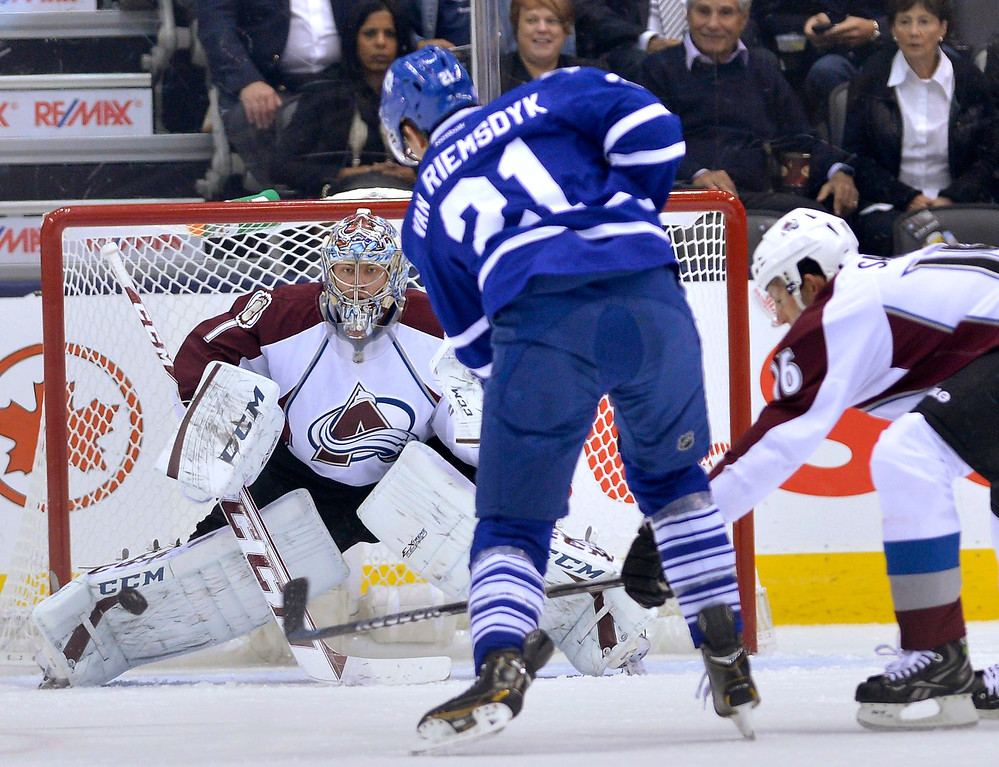 . Toronto Maple Leafs left wing James van Riemsdyk, center, takes a shot on Colorado Avalanche goalie Semyon Varlamov as Avalanche\'s Cory Sarich, right, defends during the first period of an NHL hockey game in Toronto on Tuesday, Oct. 8, 2013. (AP Photo/The Canadian Press, Nathan Denette)