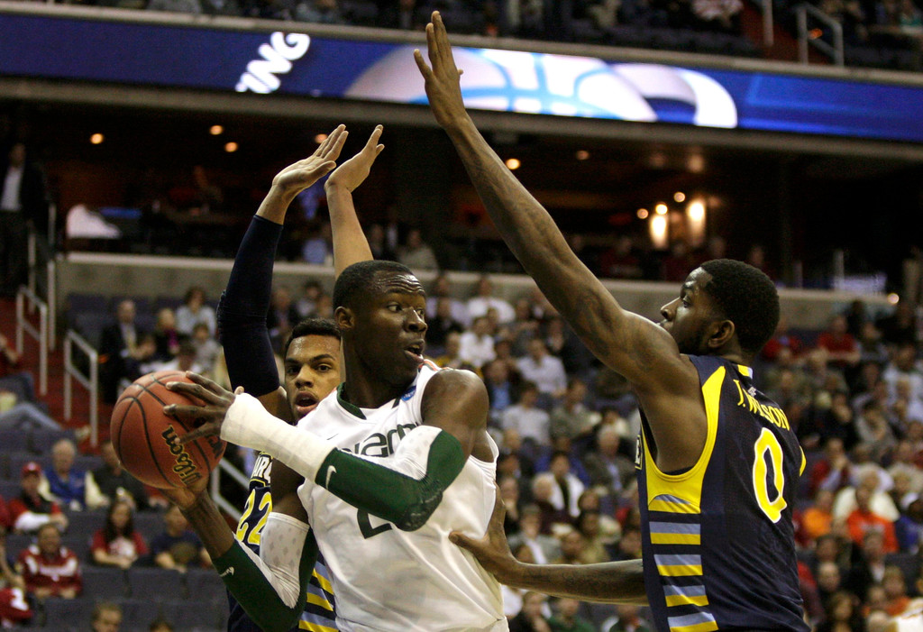 . Miami Hurricanes center Tonye Jekiri (C) is guarded by Marquette Golden Eagles guard Trent Lockett (L) and forward Jamil Wilson during the first half in their East Regional NCAA men\'s basketball game in Washington, March 28, 2013. REUTERS/Jonathan Ernst