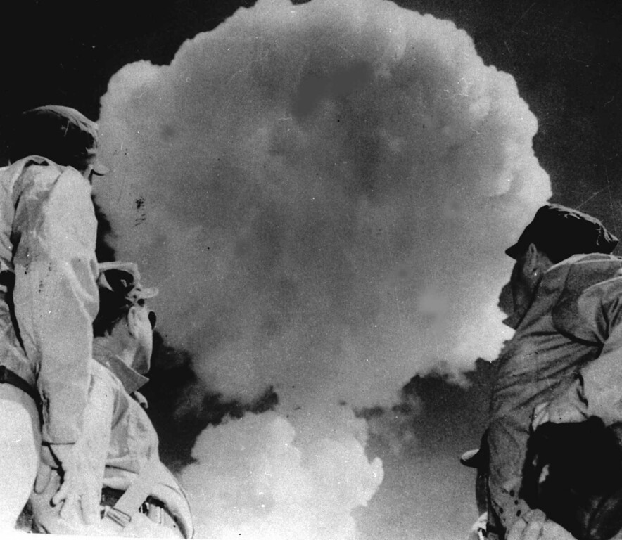 . U.S. Soldiers watch the mushroom cloud from the atomic explosion at Yucca flats in Nevada, April 22, 1952.  The atomic cloud rises into the sky shortly after the detonation.  Earlier these soldiers occupied foxholes less than five miles from ground zero.  (AP Photo)