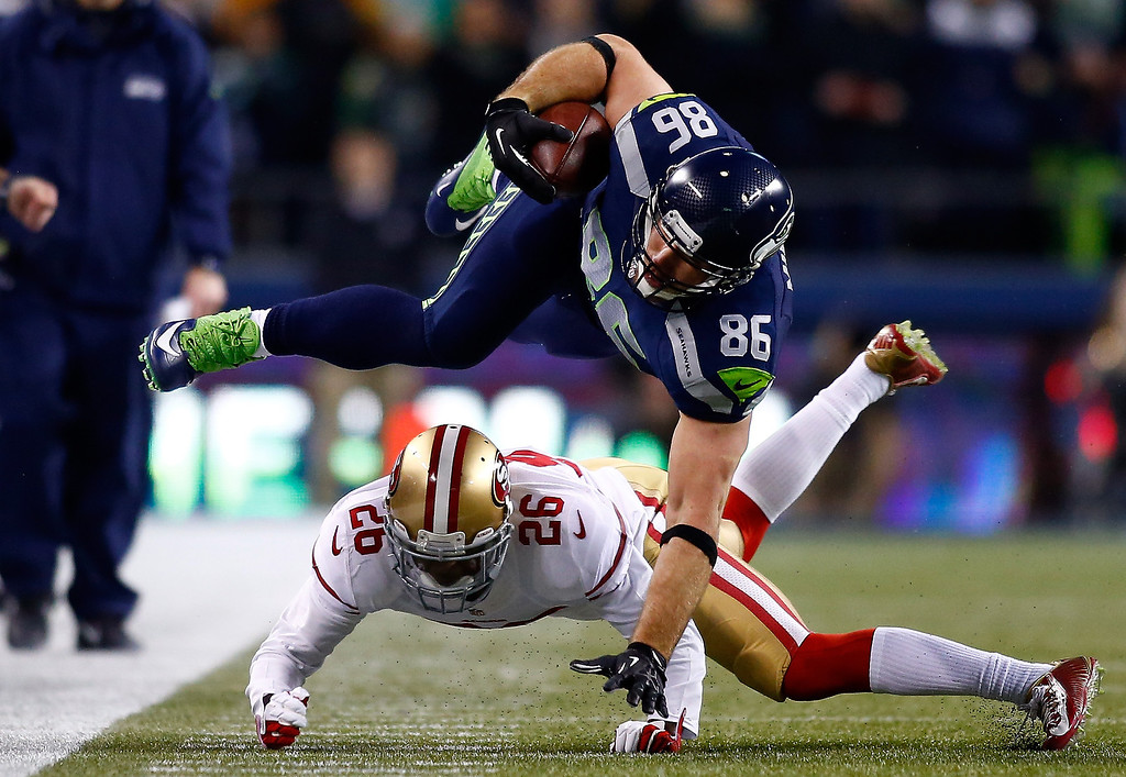 . Tight end Zach Miller #86 of the Seattle Seahawks is tackled by cornerback Tramaine Brock #26 of the San Francisco 49ers for a two-yard gain in the second quarter during the 2014 NFC Championship at CenturyLink Field on January 19, 2014 in Seattle, Washington.  (Photo by Jonathan Ferrey/Getty Images)