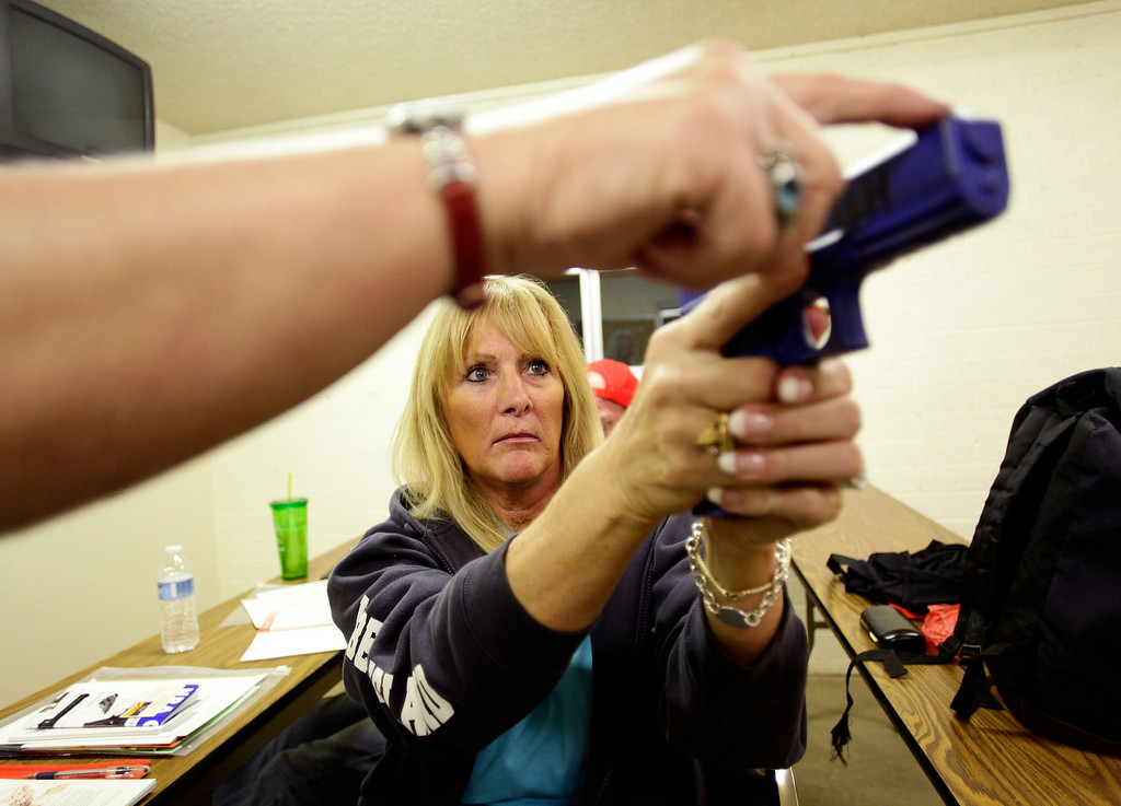 . Susan Byrne-Dewhirst learns the proper way to hold a blue dummy handgun as she attends the Arizona Women\'s Shooting Associates and NRA gun safety training class taught by certified instructor Carol Ruh at Ben Avery Shooting Facility in Phoenix, Arizona, March 13, 2013. REUTERS/Joshua Lott