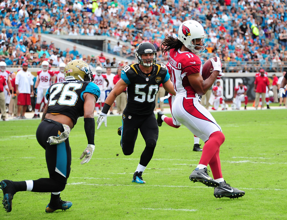 . Larry Fitzgerald #11 of the Arizona Cardinals makes a catch for a touchdown against Josh Evans #26 and Russell Allen #50 of the Jacksonville Jaguars at EverBank Field on November 17, 2013 in Jacksonville, Florida. (Photo by Scott Cunningham/Getty Images)