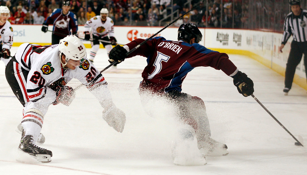 . Chicago Blackhawks left wing Brandon Saad, left, tries to stop as Colorado Avalanche defenseman Shane O\'Brien picks up a loose puck in the second period of an NHL hockey game in Denver, Friday, March 8, 2013. (AP Photo/David Zalubowski)