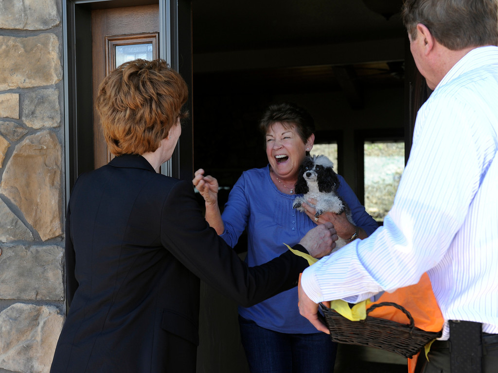 ". Cynthia Flanagan and her toy poodle ""Ruby\"" greet the mayor and his wife at the front door of their newly built home. Cynthia and her husband Bill were able to move in to the house in early April. Colorado Springs Mayor Steve Bach and his wife Suzi are making their third recent visit to homeowners in the Waldo Canyon Fire area who have rebuilt and moved in to new homes since the fire last summer. Construction can be seen everywhere, including in the Parkside subdivision that was particularly hard hit. (Photo By Kathryn Scott Osler/The Denver Post)"